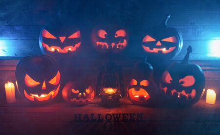 The concept of Halloween. Many Evil Scary Pumpkins in the dark with a blue ice glow. Jack Lantern amidst the darkness with a bat lamp, candles with an inscription of halloween and smoke