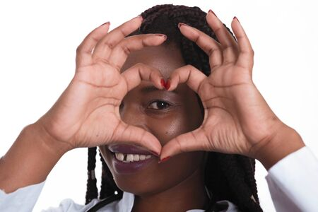 Female american african doctor, nurse woman wearing medical coat with stethoscope doing heart with hands and looking through it. Happy excited for success medical worker posing on light background isolated Banco de Imagens