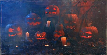 The concept of Halloween. A lot of luminous evil scary pumpkins, jack lantern, with candles, leaves and eerie branches with a warm and cold blue light on a wooden background in the smoke Imagens