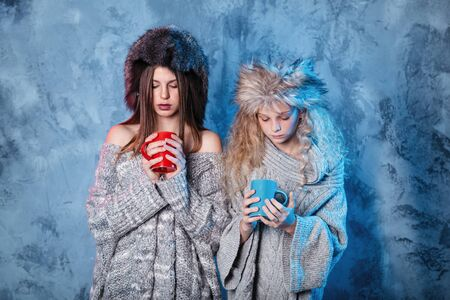 Merry Christmas and happy new year! Adorable sisters holds red and blue cups. Close portrait on gray background. Girls in fur hat and sweater looks cold Banco de Imagens