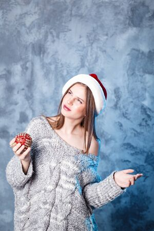 Merry Christmas and happy new year! Adorable girl with ball toy in mouth looks very puzzled. Close portrait on gray background. Girl in santa hat and sweater