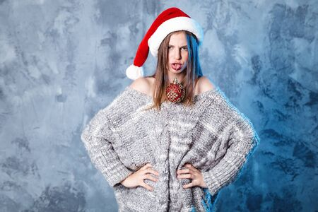 Merry Christmas and happy new year! Adorable girl with ball toy in mouth looks very cheeky. Close portrait on gray background. Girl in santa hat and sweater Banco de Imagens