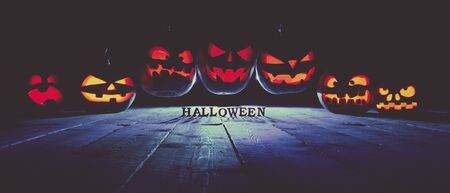 The concept of Halloween. A lot of glowing fiery light angry scary pumpkins flying through the air. Jack Lantern, with Halloween inscription, with a blue cool light behind on a wooden background Stock Photo