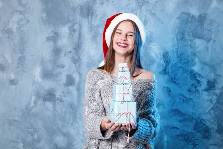 Merry Christmas and happy new year! Adorable happy girl hold many presents in hands. Close portrait on gray background. Girl in santa hat and sweater looks very pleased Banco de Imagens
