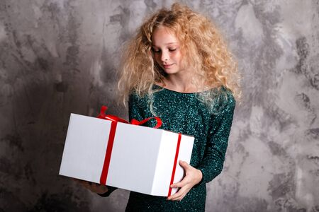 Merry Christmas and happy new year! happy girl with big present in hands thinking about gift