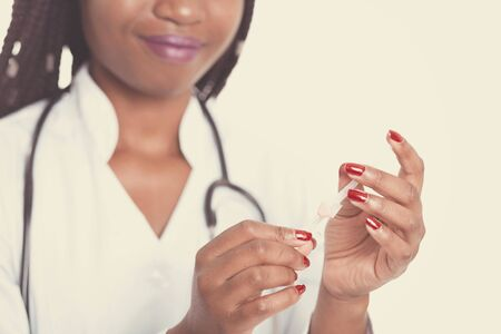 Female american african doctor, nurse woman wearing medical coat with stethoscope and needle dropper. Happy excited for success medical worker posing on light background
