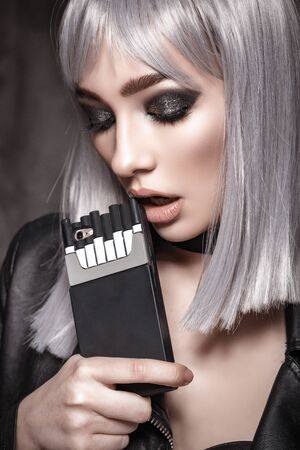 Girl in a leather jacket with white hair with big beautiful eyes in an interior loft studio with a case of a pack of cigarettes. The girl in the bra. Fashionable Female stands at the brick. Fashionable female with gray hair