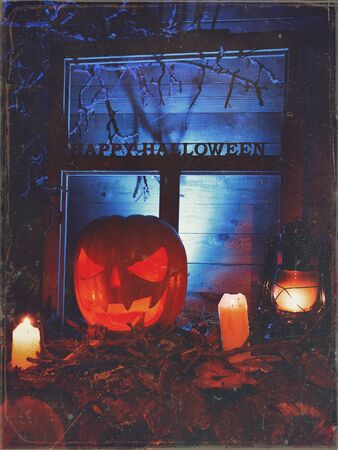 Halloween - pumpkins, candles and a lamp on leaves and logs with a warm and cold glow, against the background of a window with branches and cobwebs, with the inscription of happy halloween