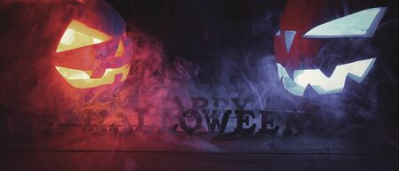 Halloween concept. Background of the holiday mystical pumpkins, jack fire, in the dark with icy blue and fiery light and smoke with the letters Happy Halloween Imagens