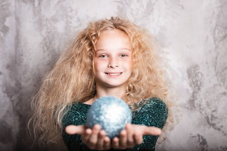 Merry Christmas and happy new year! happy girl with big ball toy in hands looks very pleased. Close portrait Banco de Imagens