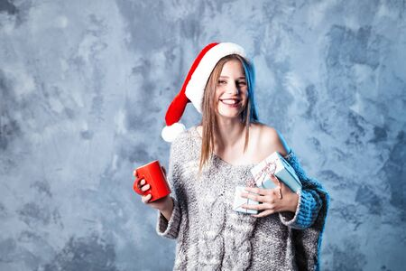 Merry Christmas and happy new year! Adorable happy girl with red cup and blue presents hold in hands. Close portrait on gray background. Girl in santa hat and sweater looks very pleased
