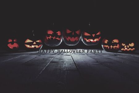 The concept of Halloween. Three glowing fiery light of evil scary pumpkins flying through the air. jack lantern, with the inscription Happy halloween party, with blue cool light behind on wooden background Stock Photo