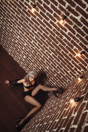 Girl in net tights and a leather jacket with long legs in the interior loft studio. Girl in a bra in high heels. Fashionable Female sits on the floor spreading her legs apart. Woman with white hair