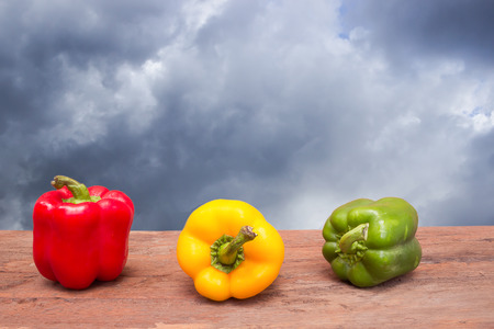 capsicum plant: Group of bell pepper on wood background Stock Photo