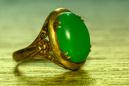 Green jade and gold ring on wood Stock Photo