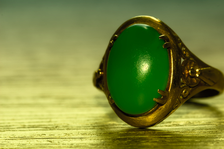 Green jade and gold ring on wood Archivio Fotografico