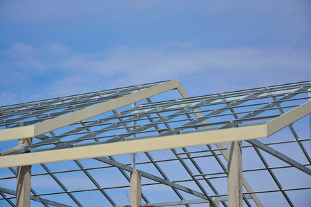 Home roof steel structure on blue sky background. Stock Photo
