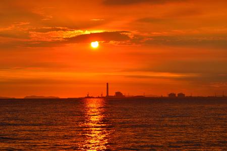 Silhouette da refinaria de petróleo está localizada na costa. Tem um fundo do pôr-do-sol