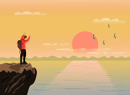 The man stood up and showed his hands on the top of the mountain happily. There are sea, mountains and sunset background
