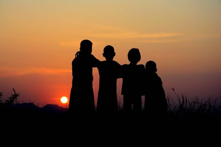 Black silhouette of four children standing together. There is a sky at sunset background