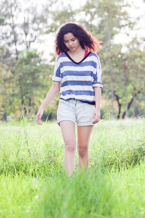 Beauty Girl Outdoors walk in grass field photo
