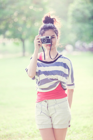 Beauty Girl Outdoors with vintage camera photo