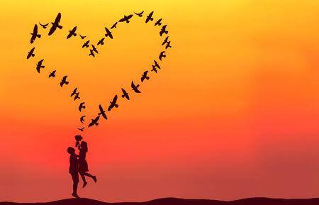 Silhouet van paar in liefde met hart gevormd door vliegende vogels. Stockfoto