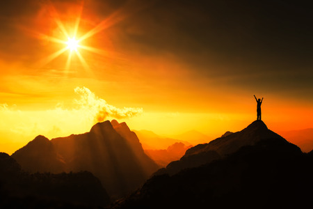 일몰과 함께 산 꼭대기에 남자의 실루엣. 개념적 장면.