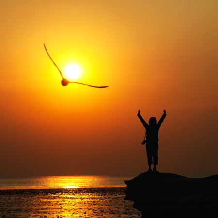 Silhouette of traveller with hands raised to birds flying in to the sun at  sunset. Stock Photo
