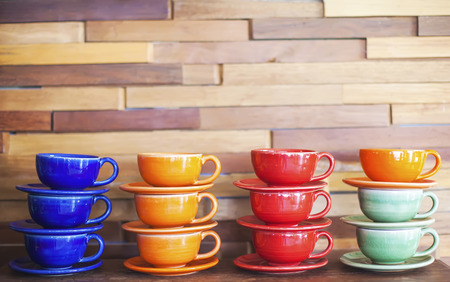 Colorful coffee cups on brick wall background Imagens