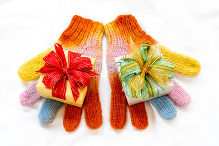 boxs: Christmas gift boxs with rainbow winter gloves on white background.