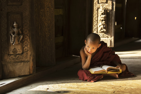 MANDALAY,MYANMAR-FEB 18 : Young monks sitting and reading at Shwenandaw Monastery is built in the traditional Burmese architectural style on February 18,2015 in Mandalay,Myanmar.