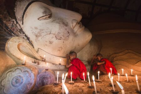 stu: BAGAN, MYANMAR - FEB 20, 2015: Southeast Asian young little Buddhist monks praying with candle light in a Buddihist temple on February 20, 2015 in Bagan, Myanmar.