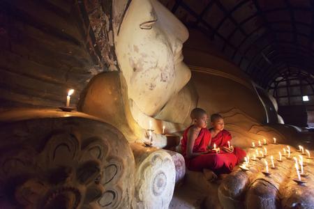 BAGAN, MYANMAR - 20 februari 2015: Zuidoost-Aziatische jonge boeddhistische monniken bidden met kaarslicht in een Buddihist-tempel op 20 februari 2015 in Bagan, Myanmar. Redactioneel