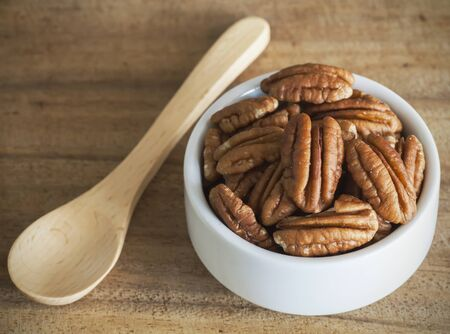 Brown pecans in white Bowl on a wood table.