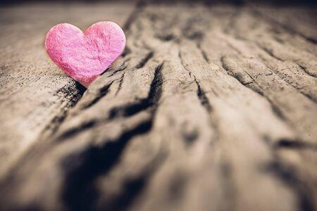 グランジの木製テーブルの上のピンクのハートとバレンタインデーの背景