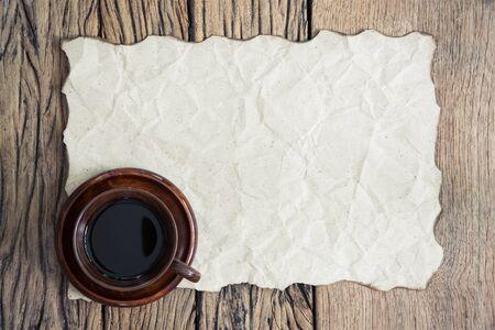 papel quemado: Taza de café y papel quemado en el fondo de madera. Retro filtrada.