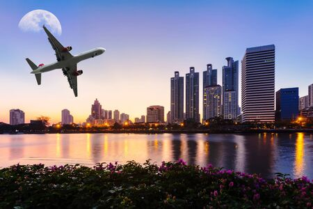 moon  metropolis: Modern building with flower, airplane and moon in the sky at twilight in Bangkok, Thailand. Stock Photo