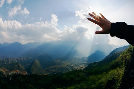 hand touch: Touch to the sun. Hand touching the sky with ray. Freedom concept. Stock Photo