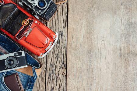 Geldbörse in der Jeanstasche und Spielzeugauto und Retro- Kameras auf hölzernem Hintergrund mit Kopienraum, Weinleseton, Reisekonzept.