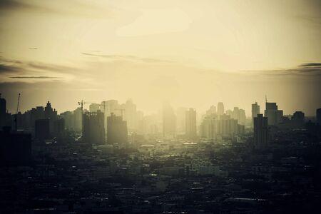 Hazy skyline of Bangkok City at dawn, smoke with sunrise. 스톡 콘텐츠