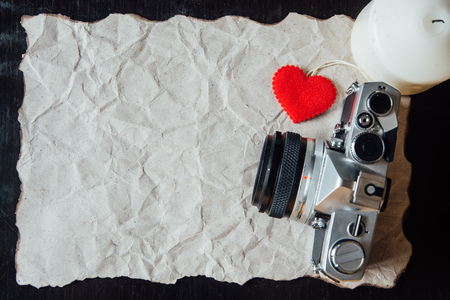 bougie coeur: Beige crumpled paper with heart, candle and vintage camera for valentine background. Banque d'images