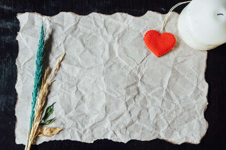 withered flower: Beige crumpled paper with heart, candle and withered flower for valentine background. Stock Photo