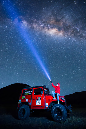 otherworldly: BROMO, INDONESIA - June 22 : 4x4 Jeep for rent with traveller among the Milky way over the bromo volcano on June 22, 2015 in Java, Indonesia. Mount Bromo is one of the most visited tourist attractions Editorial