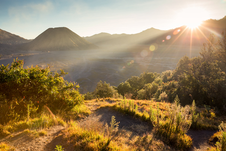 tengger: Before sunset with sun-flare at Mount Bromo volcano, the magnificent view of Mt. Bromo located in Bromo Tengger Semeru National Park, East Java, Indonesia. Stock Photo