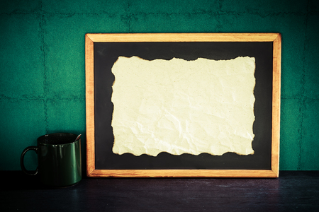 papel quemado: Still life of empty burned paper put on blackboard with coffee cup on wooden table over green wall background.