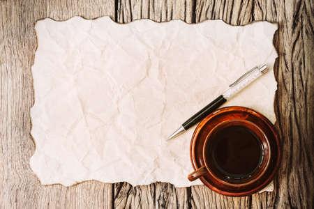 papel quemado: papel quemado en blanco con la pluma y la taza de café en la mesa de madera vieja. Foto de archivo