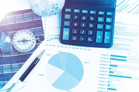 Graphs, charts, calculator, pen, compass on business table. The workplace of business people. Blue color tone.