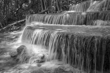 Landscape photo of beautiful waterfall in rainforest, Huay Mae Kamin Waterfall in Kanchanaburi, Thailand. Black and white tone.