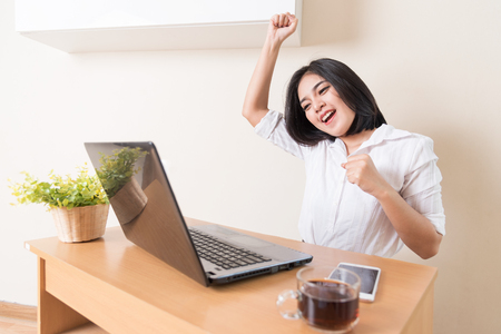 triumphing: Happy excited successful businesswoman triumphing in office.Success business concept.
